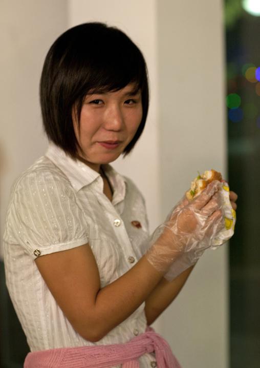 Young North Korean woman eating burger with plastic gloves at Kaeson youth park, Pyongan Province, Pyongyang, North Korea