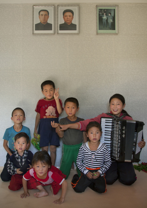Group of children posing under Kim Jong il and Kim il Sung portraits in a house, South Pyongan Province, Chonsam Cooperative Farm, North Korea