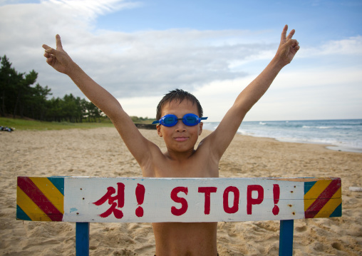 North Korean boy on a beach in front of stop sign, North Hamgyong Province, Chilbo Sea, North Korea