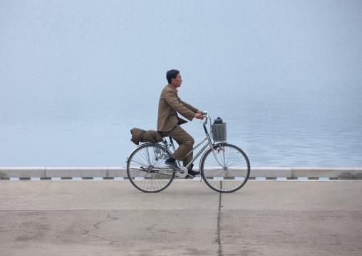 North Korean man riding a bicycle along Taedong river, Pyongan Province, Pyongyang, North Korea