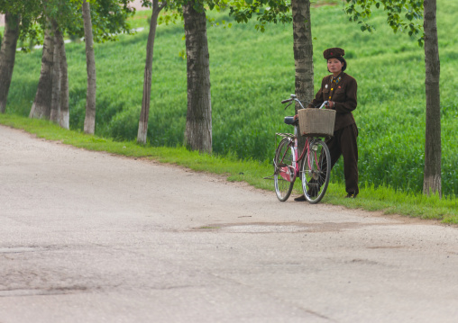 North Korean female soldier with her bicycle on the side of the road, South Pyongan Province, Nampo, North Korea