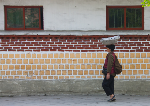 North Korean woman carrying stuff on her head in the street, North Hwanghae Province, Kaesong, North Korea
