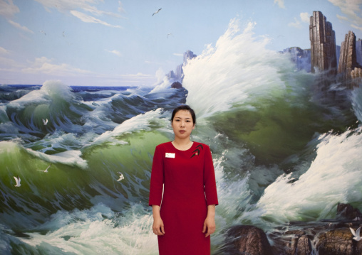 North Korean waitress in a restaurant in front of a mural painting, South Pyongan Province, Nampo, North Korea