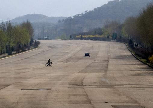 North Korean man with a bicyle crossing an empty highway in North Korea, Pyongan Province, Pyongyang, North Korea
