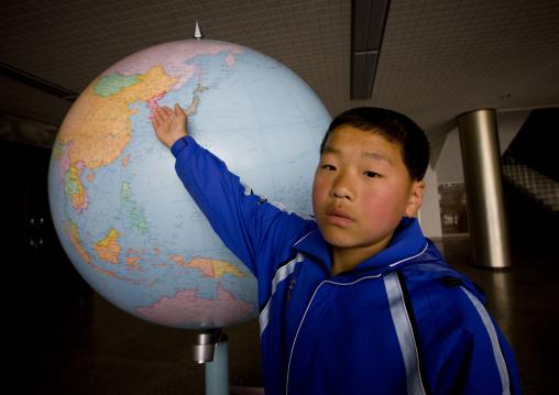 North Korean boy showing North Korea on a world map in Songdowon international children's camp, Kangwon Province, Wonsan, North Korea