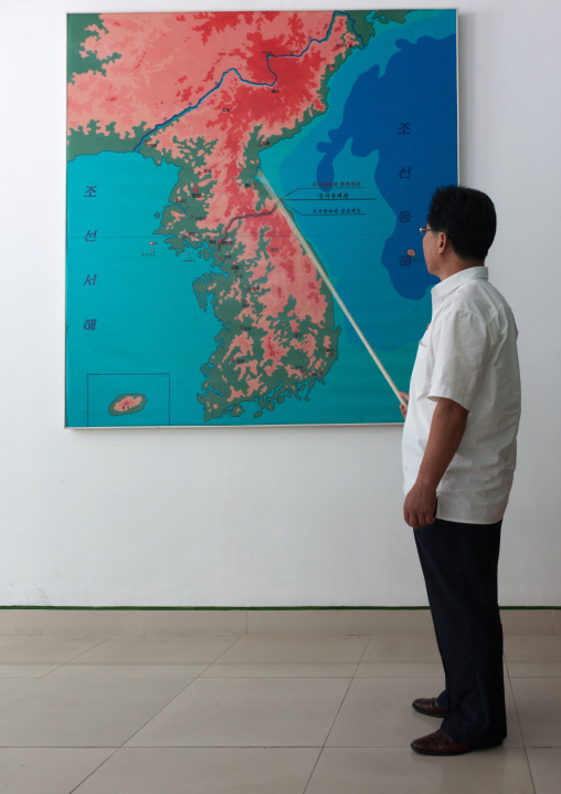 North Korean guide in front of the Korea map on the Demilitarized Zone, North Hwanghae Province, Panmunjom, North Korea