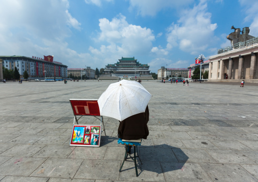 North Korean photographer waiting under an umbrella in Kim il Sung square, Pyongan Province, Pyongyang, North Korea