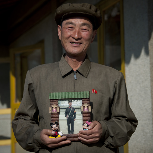 North Korean man showing his son picture serving in the army in a Mickey mouse frame, North Hamgyong Province, Jung Pyong Ri, North Korea