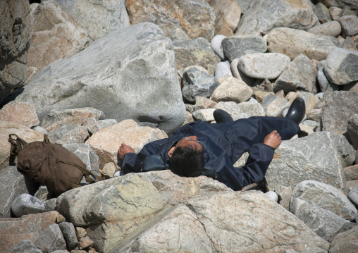 North Korean man sleeping on rocks under the sun, North Hamgyong Province, Chilbo Sea, North Korea