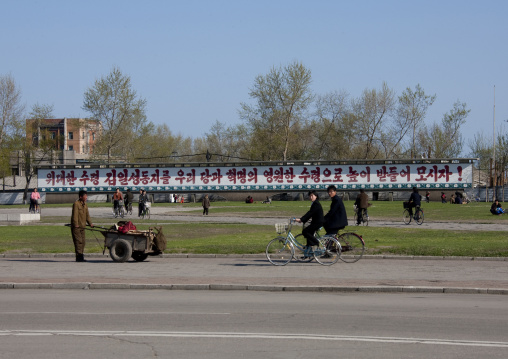 North Korean cyclists in a street in front of a propaganda billboard, North Hamgyong Province, Chongjin, North Korea