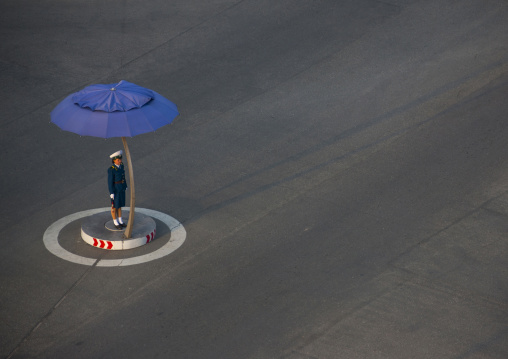 North Korean traffic security officer in blue uniform in the street, Pyongan Province, Pyongyang, North Korea