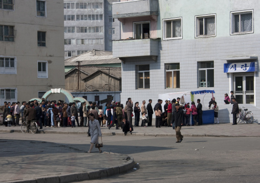 North Korean people queuing to buy food and drinks in a small street shop, Pyongan Province, Pyongyang, North Korea