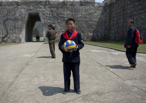 North Korean pioneer holding a ball in his hands, Pyongan Province, Pyongyang, North Korea
