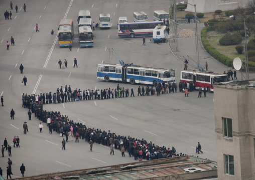 Crowd of North Korean people queueing in line for a bus
