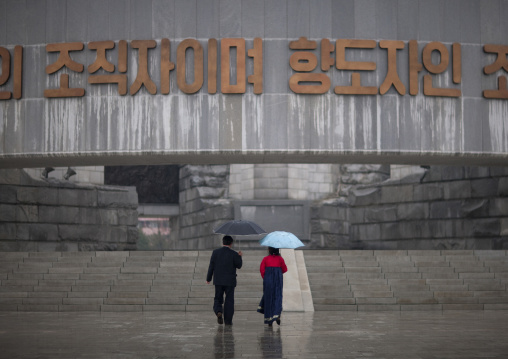North Korean man and woman under an umbrella going to the monument to Party founding, Pyongan Province, Pyongyang, North Korea