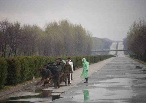 North Korean men repairing holes on an empty highway under the rain, Pyongan Province, Pyongyang, North Korea