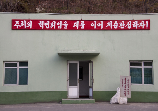 Propaganda slogan above the entrance of a building saying let us accomplish the succession by continuing the great revolutionary success of juche!, Ryanggang Province, Samjiyon, North Korea