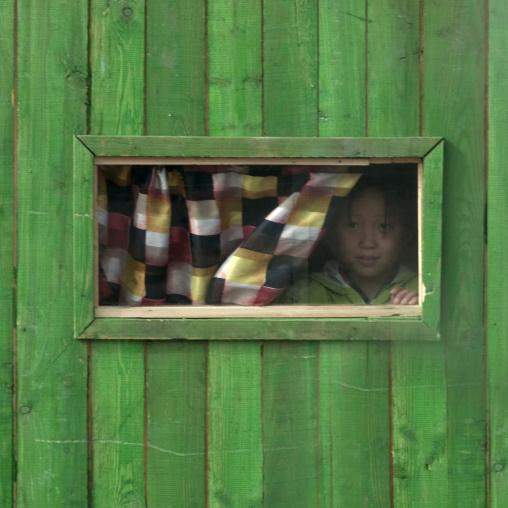 North Korean girl looking thru the window of a small green shop, Ryanggang Province, Samjiyon, North Korea