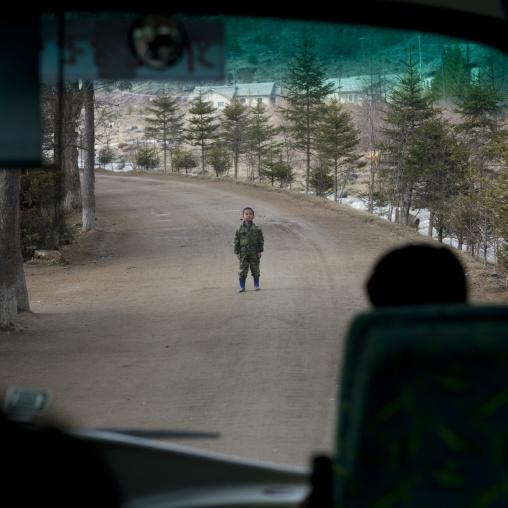North Korean boy standing in the middle of the road in front a bus, Ryanggang Province, Rimyongsu, North Korea