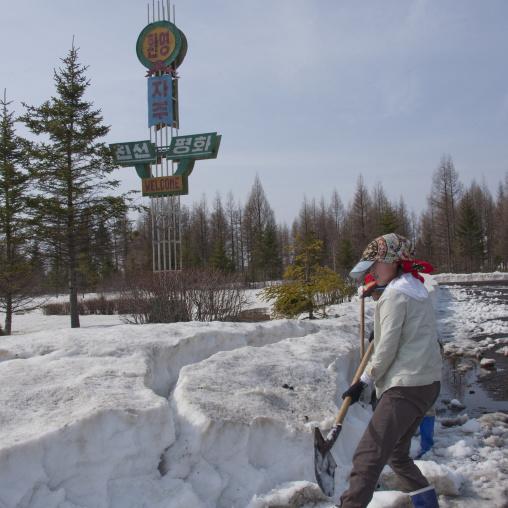 Girls clearing snow from the road in front of pegaebong hotel, Ryanggang Province, Samjiyon, North Korea