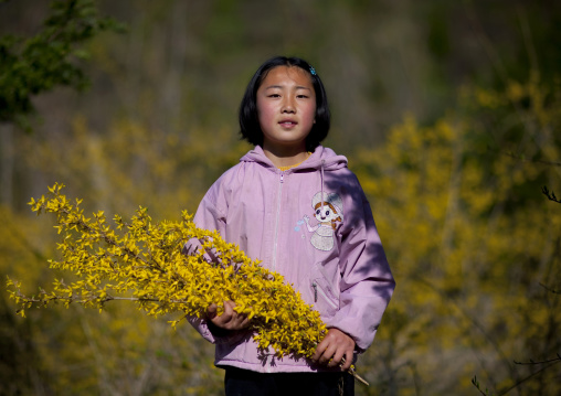 Portrait of a North Korean girl holding flowers, North Hamgyong Province, Jung Pyong Ri, North Korea