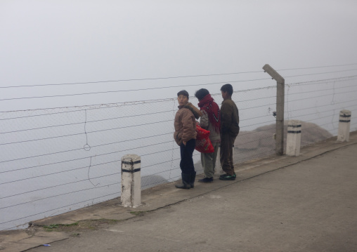 North Korean people looking through barbed wire on the coastline in the fog, Kangwon Province, Wonsan, North Korea
