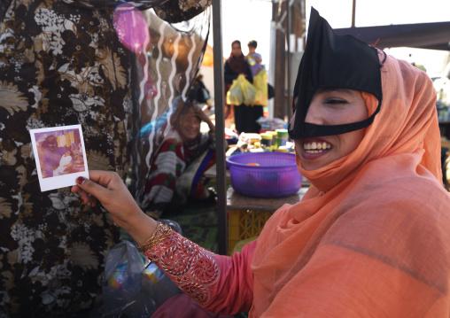 Bedouin Woman Showing A Polaroid Photo In Ibra, Oman