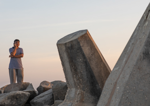 Man speaking on a mobile phone on a jetty, Dhofar Governorate, Mirbat, Oman