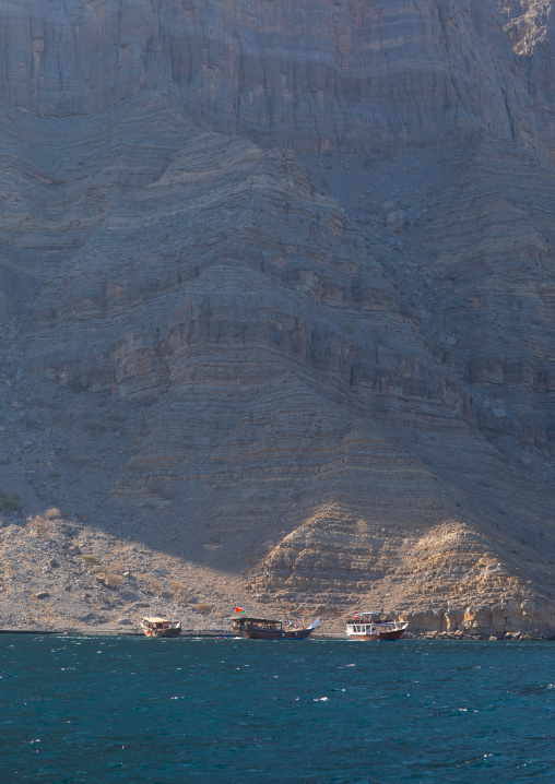 Dhow sailing in the fjords in front of mountains, Musandam Governorate, Khasab, Oman