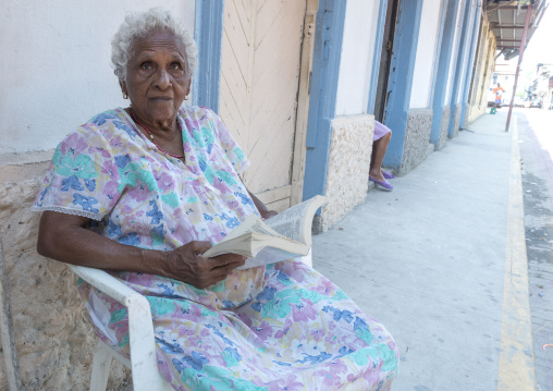 Panama, Province Of Panama, Panama City, Old Panamean Woman Reading In Front Of Her House In The Street In Casco Viejo