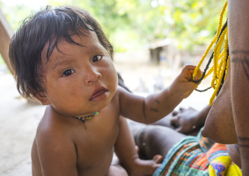 Panama, Darien Province, Bajo Chiquito, Embera Tribe Baby Playing With Necklaces