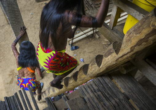 Panama, Darien Province, Bajo Chiquito, Embera Tribe Women Climbing A Ladder In A House