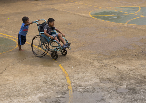 Panama, Darien Province, Bajo Chiquito, Embera Tribe Kids Playing With A Wheelchair