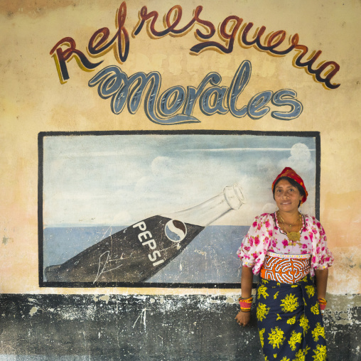 Panama, San Blas Islands, Mamitupu, Kuna Tribe Woman In Front Of A Pepsi Advertising