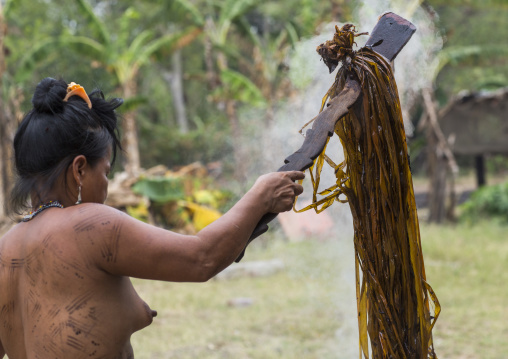 Panama, Darien Province, Puerta Lara, Wounaan Tribe Woman Usinf A Special Wood Stick To Dye Clothes