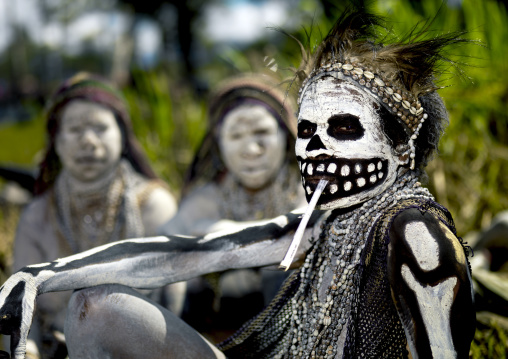 Skeleton tribe woman smoking during a sing sing, Western Highlands Province, Mount Hagen, Papua New Guinea