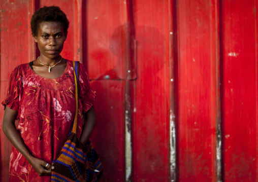 Woman in front of a red wall, East New Britain Province, Rabaul, Papua New Guinea