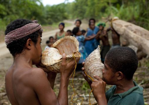 Boys blowing in shells to call friends, Milne Bay Province, Alotau, Papua New Guinea