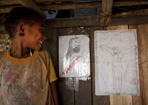 Girl looking at jesus christ drawings on a wall, Milne Bay Province, Trobriand Island, Papua New Guinea