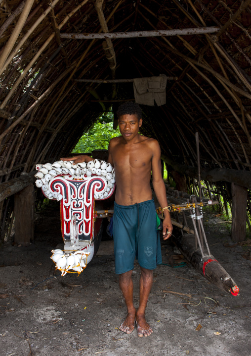 Man in front of kula canoe decorated with shells, Milne Bay Province, Trobriand Island, Papua New Guinea