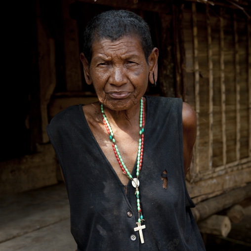Old woman with a christian cross, Milne Bay Province, Trobriand Island, Papua New Guinea