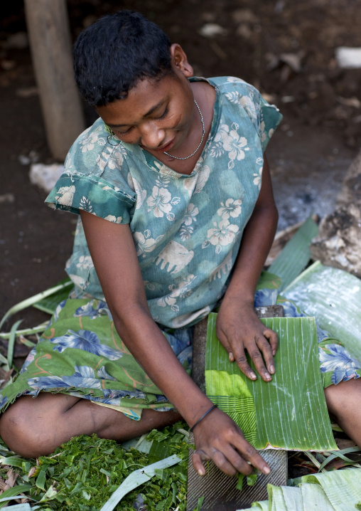 Girl making Doba traditional money with banana leaves on a wooden board, Milne Bay Province, Trobriand Island, Papua New Guinea