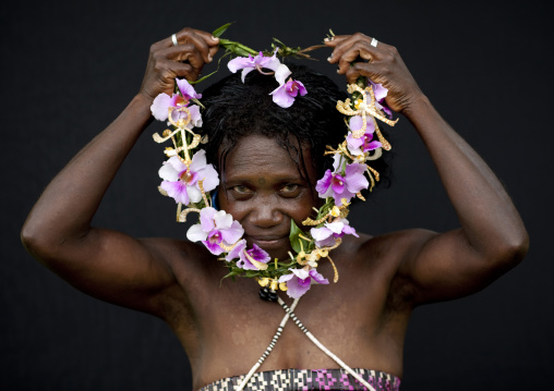 Woman putting a floral necklace around her neck, Autonomous Region of Bougainville, Bougainville, Papua New Guinea