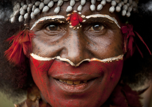 Papuan woman with red tribal makeup on the face, Western Highlands Province, Mount Hagen, Papua New Guinea