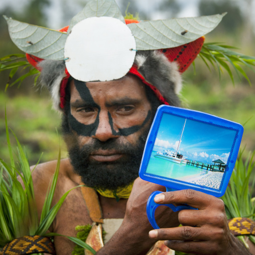 Hagener warrior putting makeup on his face and looking in a mirror, Western Highlands Province, Mount Hagen, Papua New Guinea