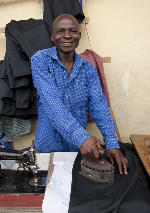Rwandan man ironing in the market, Lake Kivu, Gisenye, Rwanda