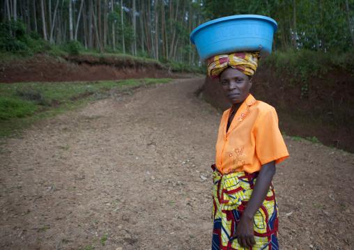 Batwa woman carrying bucket on her head, Western Province, Cyamudongo, Rwanda