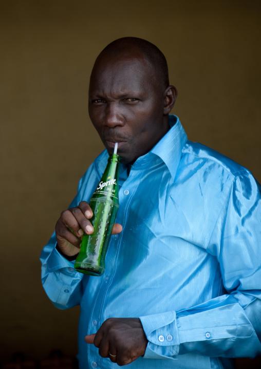 Rwandan man drinking a sprite drink with a straw, Kigali Province, Kigali, Rwanda