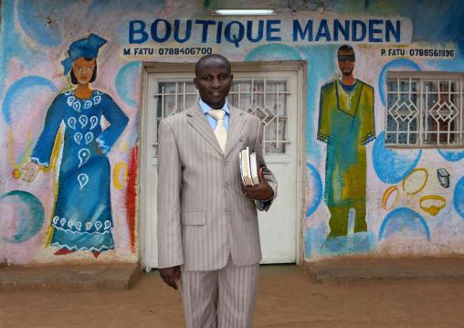 Rwandan man in front of a tailor shop mural, Kigali Province, Kigali, Rwanda