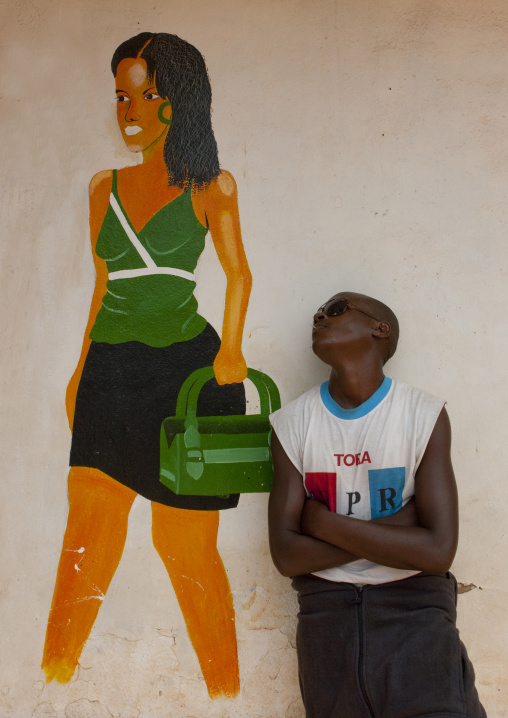 Rwandan man in front of a shop mural, Kigali Province, Kigali, Rwanda